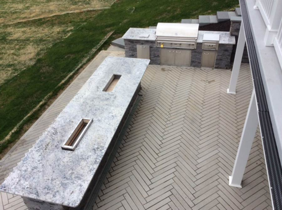 The placement of the outdoor kitchen featuring a stainless steel high end Robata Japanese grill was key to the entire project because it also serves to correct the problem of a downward slope at the side of the patio that needed to be addressed